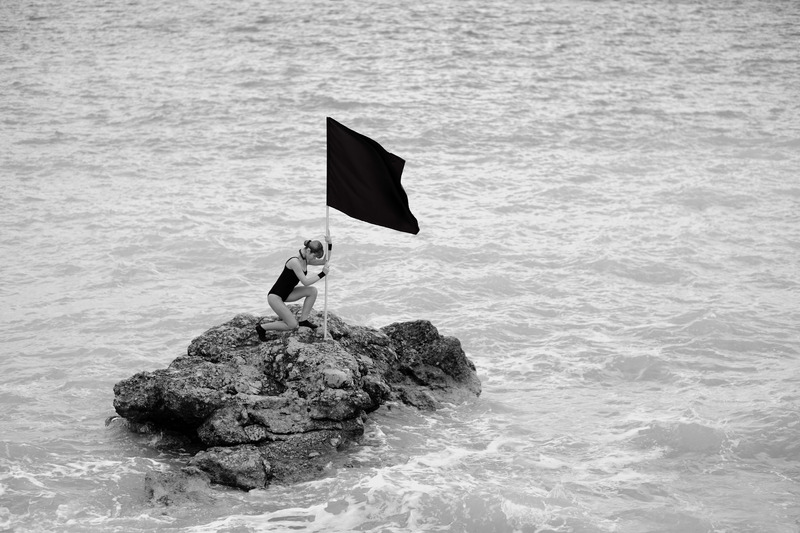 Woman on rock formation holding a flag.
